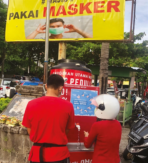 A couple wash their hands at one of thousands of free hand washing stations set up across Bali under a sign that says masks are compulsory at this wet market in the capital Denpasar.